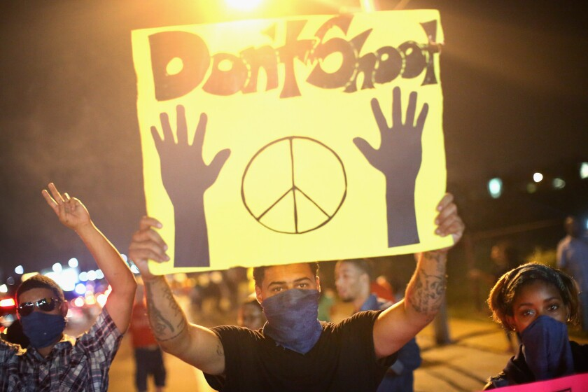"Demonstrators hold up a ""Don't shoot"" sign during an Aug. 17 protest over the killing of Michael Brown in Ferguson, Mo."