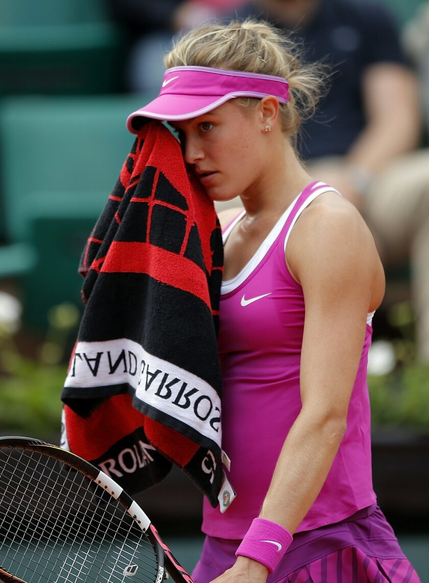 CAPTION CORRECTION, CORRECTS FINAL SCORE IN SECOND SENTENCE - Canada's Eugenie Bouchard wipes her face as she plays France's Kristina Mladenovic during their first round match of the French Open tennis tournament at the Roland Garros stadium, Tuesday, May 26, 2015 in Paris. Mladenovic won 6-4, 6-4. (AP Photo/Francois Mori)