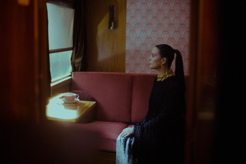"""A behind-the-scenes photo of Jessie Ware filming the video for """"Spotlight"""" in a train car"""