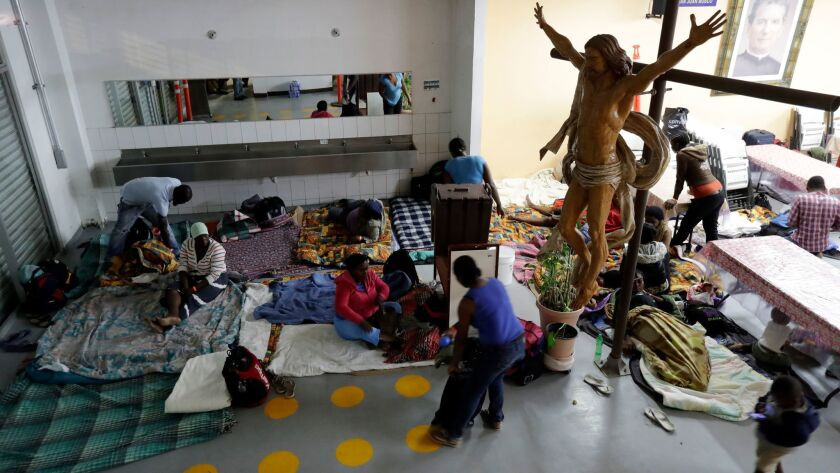 Haitian women and children prepare on Monday to sleep on the floor of the Padre Chava migrant shelter in Tijuana.