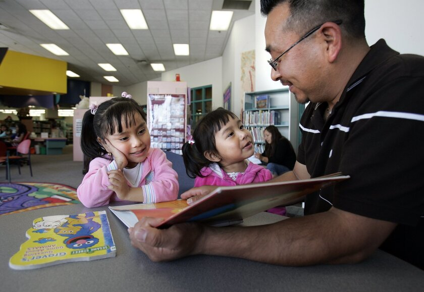 Gerardo Pena reads to his daughters, Jacqueline Pena, 4, (left) and Alexa Pena, 2, at the East Valley Branch Library.