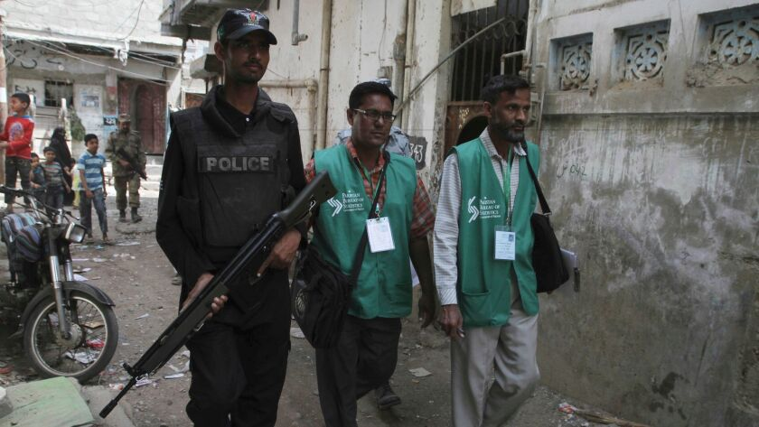 A police officer escorts government workers through the slums of Karachi, Pakistan, to collect data during the country's first census since 1988.