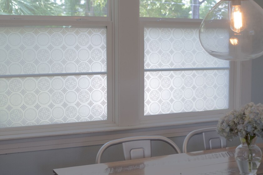 This photo shows StickPretty Gothica window film which shields street views from this family kitchen table while still allowing tree-filled sight lines. Renters have traditionally been limited in how boldly they can decorate and still get their security deposit back. But new products are making renters' decorating dreams more doable. (Christy Flannigan/StickPretty via AP)