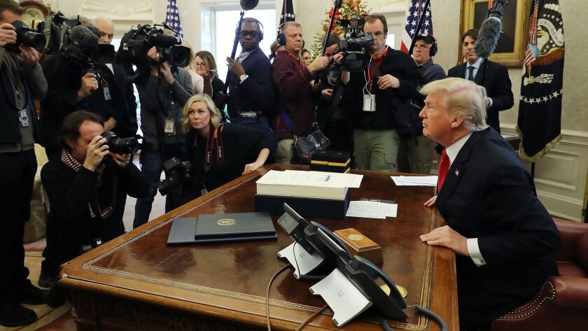 President Trump talks with journalists after signing tax reform legislation in the Oval Office in December 2017.