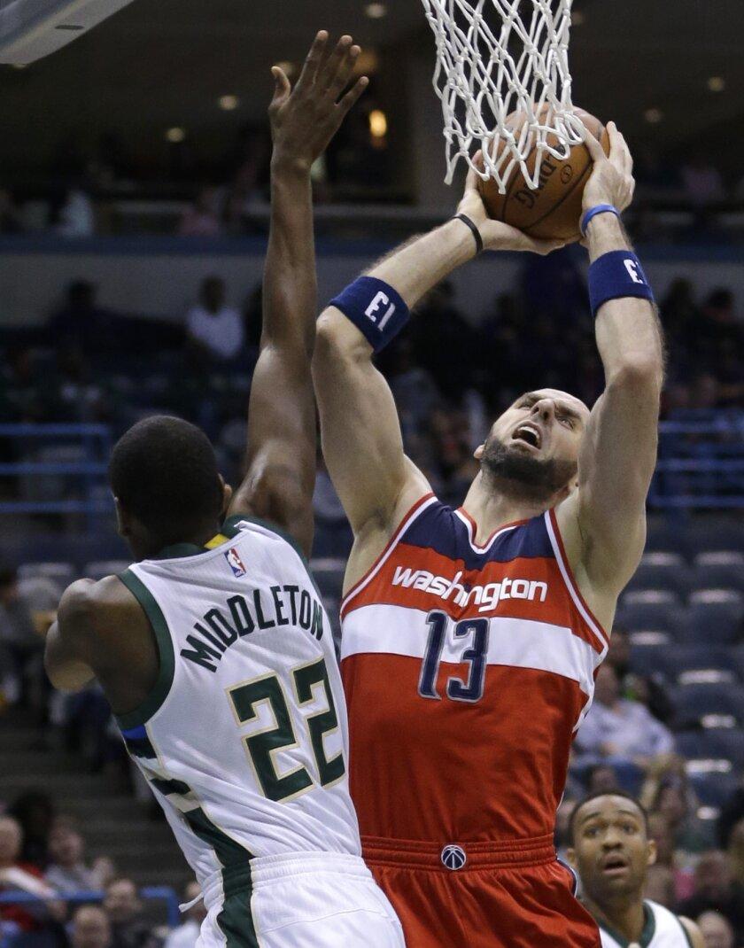 Washington Wizards' Marcin Gortat (13) goes up for a shot against Milwaukee Bucks' Khris Middleton (22) during an NBA basketball game Thursday, Feb. 11, 2016, in Milwaukee. (AP Photo/Aaron Gash)