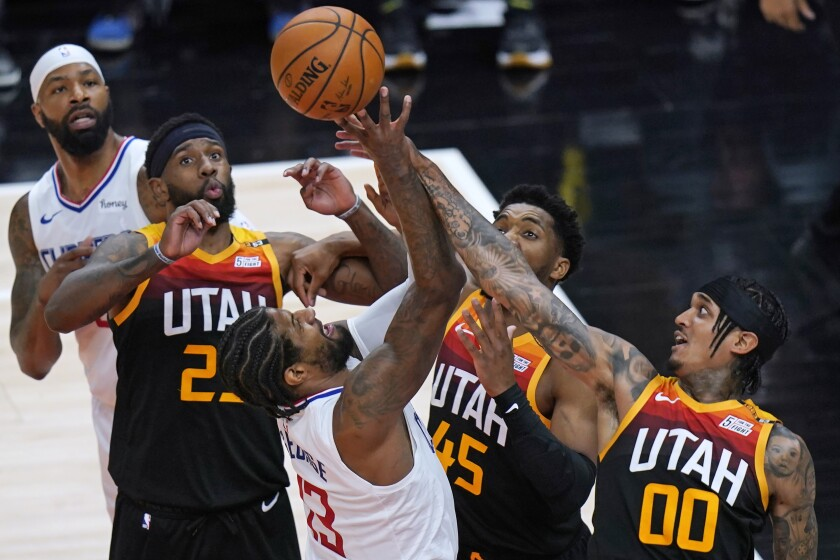 Clippers forward Paul George tries to score  against the Jazz defense.