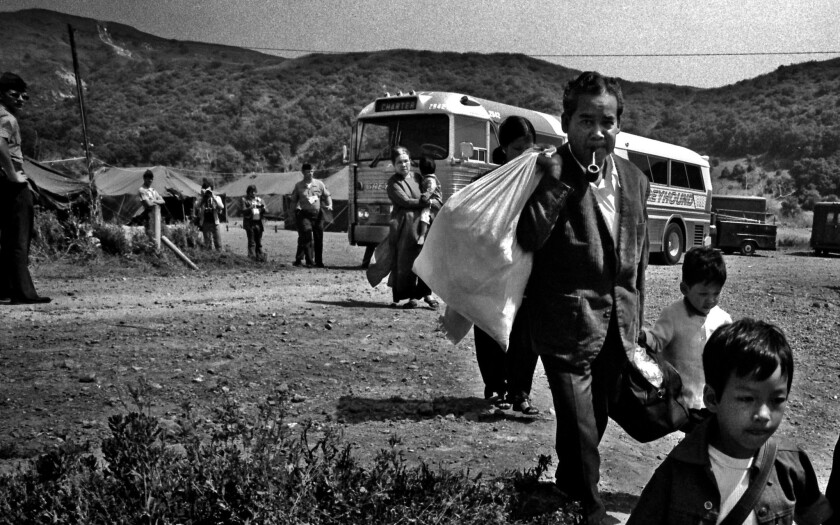 Vietnamese refugees file off a Greyhound bus at the Camp Talega relocation center at Camp Pendleton on June 12, 1975.