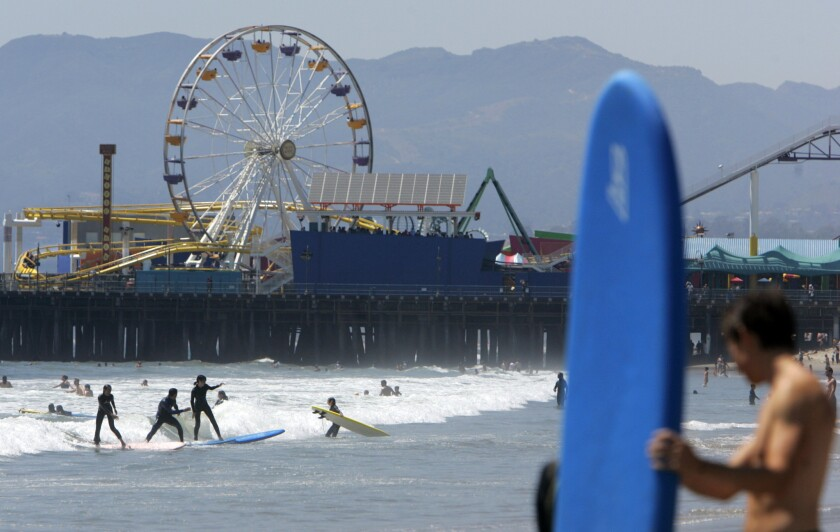 Surfers hit the ocean near the Santa Monica Pier, a few blocks from where the Expo Line will stop.