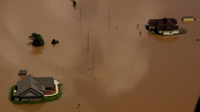 In this Sept. 1, 2017 photo, homes are submerged by water from the flooded Brazos River in the after