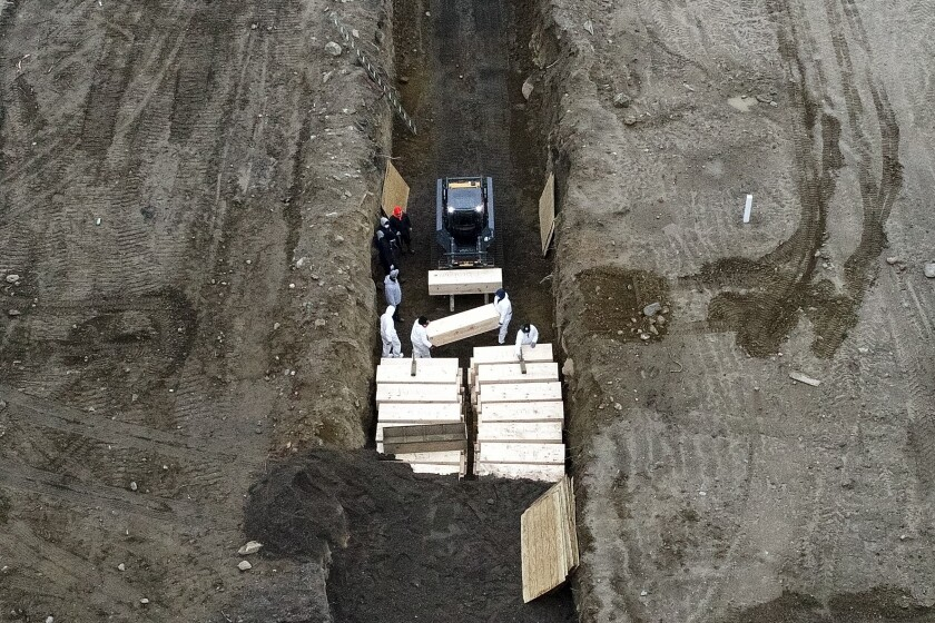 Workers bury coffins in a trench