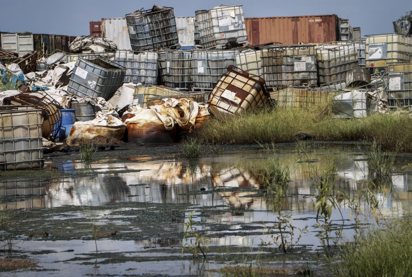 Containers used for hazardous chemicals are piled up at a junkyard near Paloch, South Sudan, in 2018.