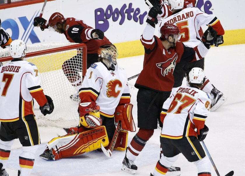 Arizona Coyotes' Anthony Duclair (10) celebrates his goal against Calgary Flames' Jonas Hiller (1), of Switzerland, as Coyotes' Martin Hanzal, second from right, joins the celebration while Flames' T.J. Brodie (7) and Michael Frolik (67), of the Czech Republic, look on during the second period of a