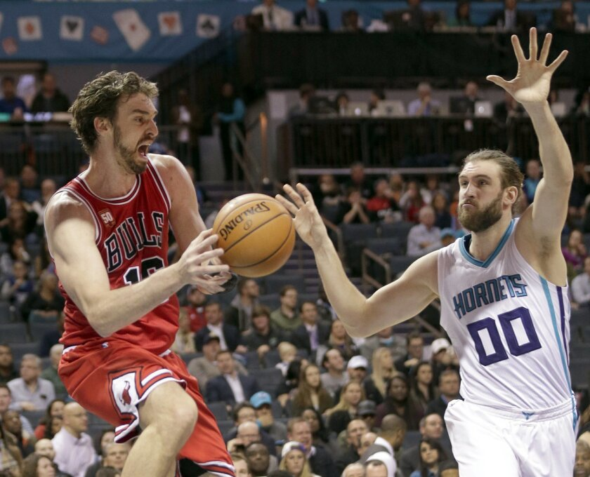 Chicago Bulls' Pau Gasol, left, looks to pass as Charlotte Hornets' Spencer Hawes, right, defends in the first half of an NBA basketball game in Charlotte, N.C., Monday, Feb. 8, 2016. (AP Photo/Chuck Burton)