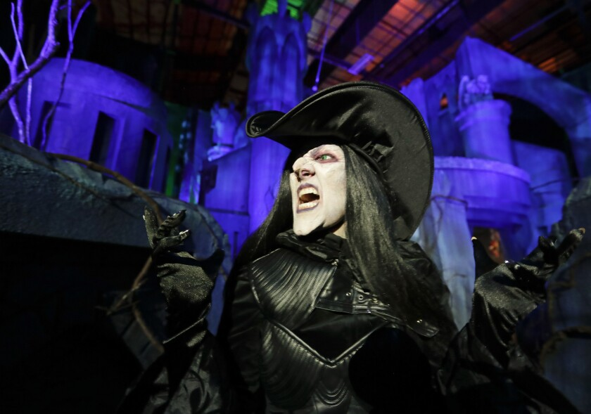 FILE - In this Sept. 12, 2018 file photo, Laura Law performs as a witch at the Scary Tales haunted house at Halloween Horror nights at Universal Studios in Orlando, Fla. After a pandemic-related absence of almost two years, Universal Orlando Resort's celebration of all things scary opened for screams on Friday, Sept. 3, 2021. Halloween Horror Nights kicked off at the Florida theme park resort for a 30th year of disturbing haunted houses, live entertainment and celebrations of pop-culture scares. (AP Photo/John Raoux, File)