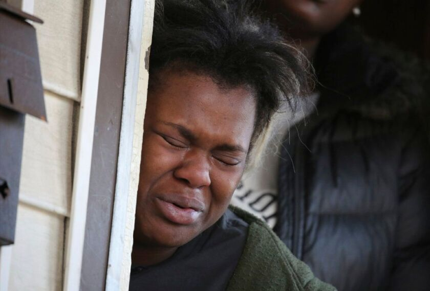 In this Tuesday, Nov. 20, 2018 photo, Tatiana Ingram, left, cries as others speak about her sister Sandra Parks, a 13-year-old girl who was killed in her bedroom when shots were fired the night before into her home in Milwaukee.