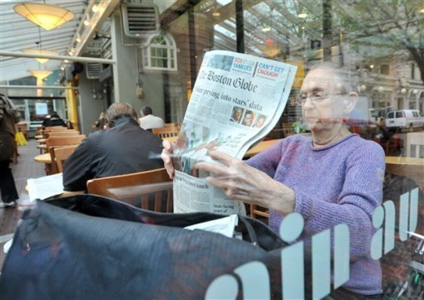 Cyn Goodenough, of Cambridge, Mass., reads the Boston Globe at a coffee shop in Harvard Square in Cambridge, Mass., Wednesday, May 6, 2009. The Boston Globe and its largest employees union reached a tentative agreement early Wednesday morning on concessions that will keep the 137-year-old newspaper publishing. (AP Photo/Josh Reynolds)