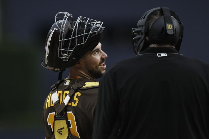 San Diego Padres catcher Austin Hedges talks with home plate umpire Gary Cederstrom during the first inning of a baseball game against the Washington Nationals Friday, June 7, 2019, in San Diego.