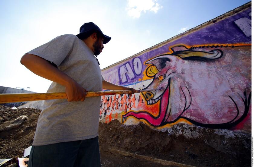 """Con el """"Mural de la Hermandad"""" artistas y voluntarios comenzaron a ponerle color a la oxidada barda fronteriza que separa a México y Estados Unidos."""