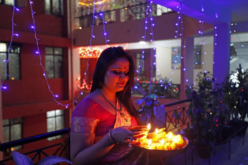 A woman holds a tray filled with earthen lamps during Diwali celebrations in Allahabad, India.