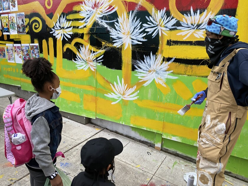 """Malcolm Procter talks with children viewing his mural on plywood in Seattle's """"autonomous zone."""""""