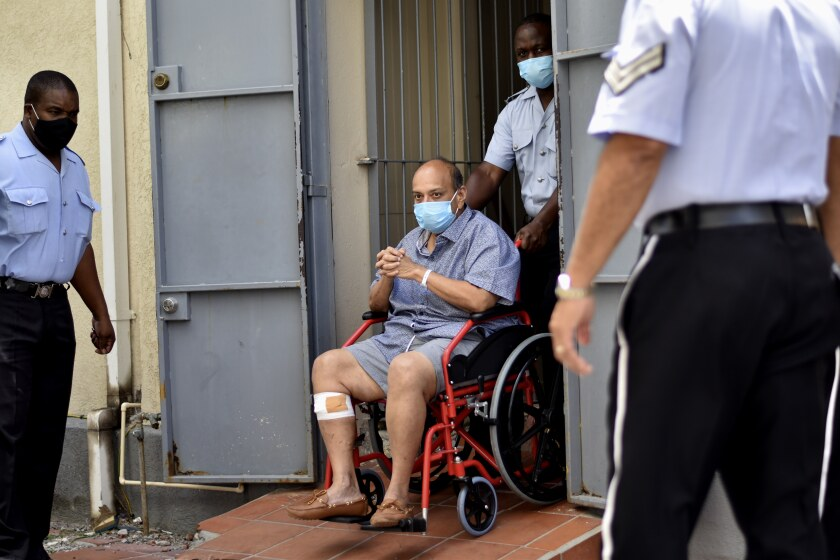 Antigua and Barbuda businessman Mehul Choksi exits in a wheelchair the magistrate's court in Roseau, Dominica, Friday, June 4, 2021. Choksi is wanted in his native India on a string of charges that include corruption, money laundering and criminal conspiracy. The fugitive was arrested May 24 on the neighboring island of Dominica accused of illegal entry. (AP Photo/Clyde Jno Baptiste)