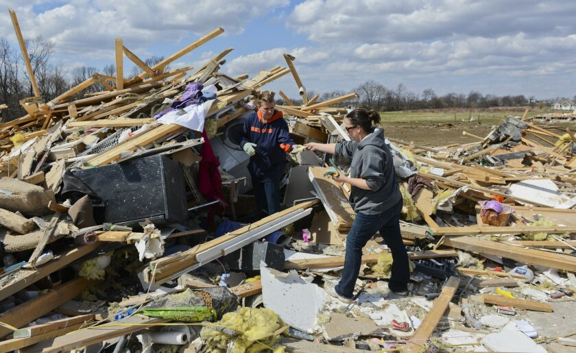 John Whitaker, left, gets help cleaning remnants of his home from volunteer Jenn Van Hise in the Cherry Hill subdivision outside of Flagg Center, Ill., on Friday, April 10, 2015. The National Weather Service says at least two tornadoes churned through six north-central Illinois counties. (AP Photo/Matt Marton)