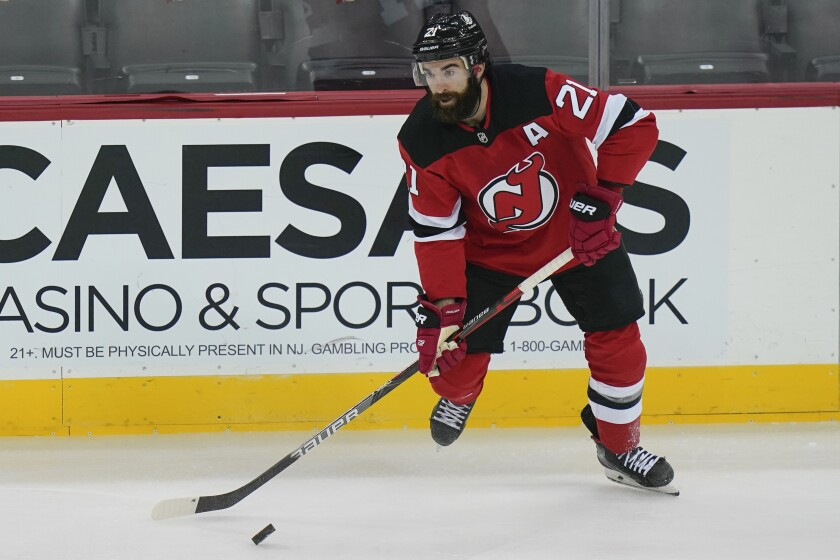FILE - New Jersey Devils' Kyle Palmieri (21) moves the puck during the first period of an NHL hockey game against the Philadelphia Flyers in Newark, N.J., in this Thursday, Jan. 28, 2021, file photo. The NHL trade deadline is less than a week away and players such as Taylor Hall, Kyle Palmieri, Mikael Granlund and Mattias Ekholm are potentially available for teams willing to make a deal. (AP Photo/Frank Franklin II, File)