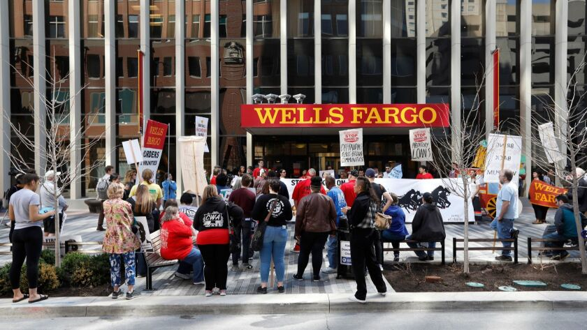 Protesters rally outside the Wells Fargo bank downtown branch April 24 in Des Moines. Late Tuesday, a federal judge in San Francisco signed off on a $480 million settlement in a class-action shareholder lawsuit over the bank's unauthorized-accounts scandal.
