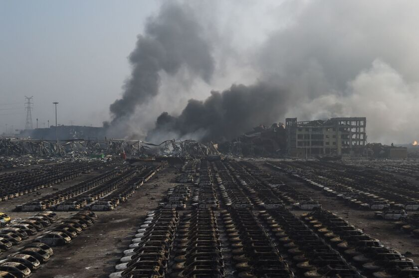 Smoke billows behind rows of burnt-out cars at the site of a series of explosions in Tianjin, northern China, in August.