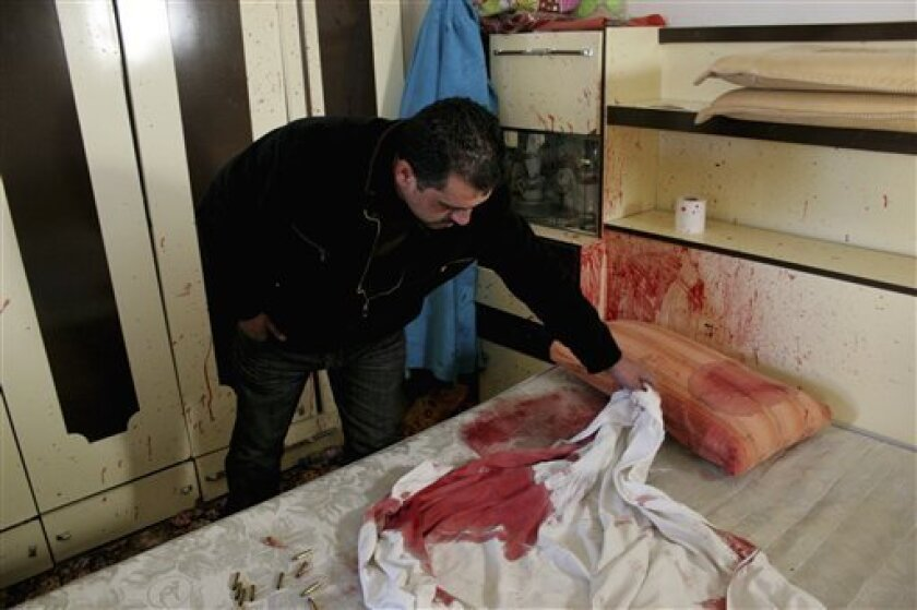 A Palestinian man examines a bloodstained bed and shell casings in the bedroom of Omar Kawasmeh in the West Bank city of Hebron, Friday, Jan. 7, 2011. Israeli troops mistakenly shot and killed a 65-year-old Palestinian man Friday during a predawn raid to arrest a Hamas militant in the West Bank, Palestinian officials said. (AP Photo/Nasser Shiyoukhi)