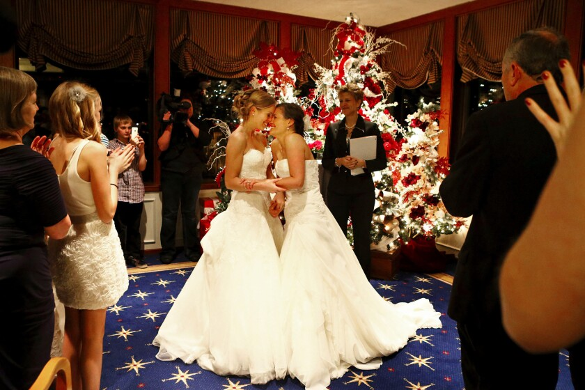 """Mary Davidson, 27, left, and Monica Rozgay, 29, smile after saying """"I do"""" at their midnight wedding at the Seattle Yacht Club. Rozgay and Davidson, of Seattle, Wash., are one of the first couples to wed following the passage of Referendum 74, which approved a bill legalizing same-sex marriage in the state."""
