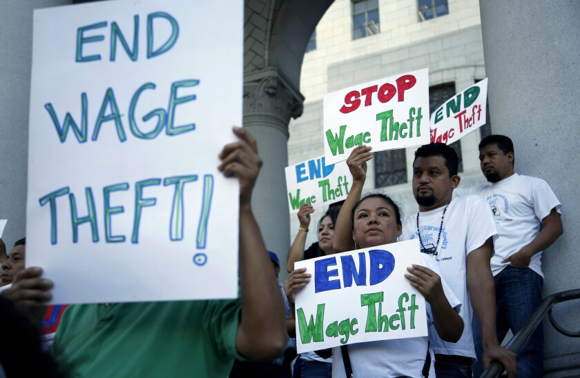 Workers appear at a news conference at Los Angeles City Hall last year to urge support for a boost in the minimum wage as well as wage-theft protections.