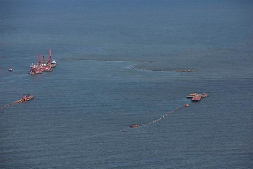La draga 'California' (i, arriba) flota junto a las islas Chandeleur (EEUU), el 23 de junio de 2010, mientras prosigue la batalla del Estado de Luisiana y el Gobierno federal por la construcción de barreras de arena que protejan la costa de Luisiana y su frágil ecosistema del vertido de crudo. EFE/Archivo