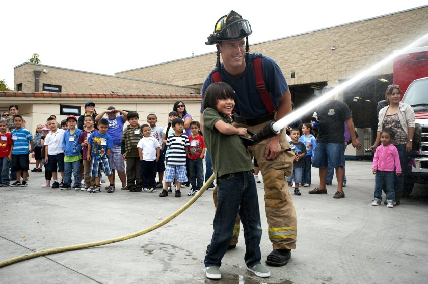 Firefighter Steve Rhoads of Station 29 in San Ysidro helps 6-year-old Edgar Arce spray a fire hose during a field trip last week for students from Willow Elementary School. Hispanics like Edgar accounted for 45 percent of children ages 5 to 17 in the county last year. Meg Roussos • U-T