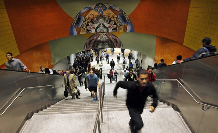 Commuters stream through the entrance of the Metro Red Line station in North Hollywood.