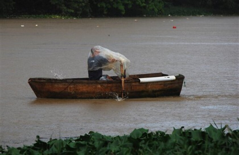 A man rowing a boat on the Ozama River protects himself with plastic as rain brought by the outer bands of Tropical Storm Chantal falls in Santo Domingo, Dominican Republic, Tuesday, July 9, 2013.  Tropical Storm Chantal threatened to turn into a hurricane while it churned toward the Dominican Repu
