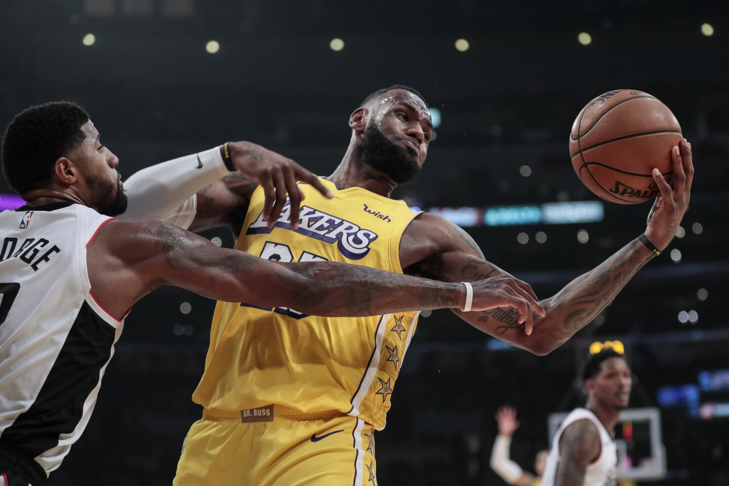 LOS ANGELES, CA, WEDNESDAY, DECEMBER 25, 2019 - Los Angeles Lakers forward LeBron James (23) controls a rebound against LA Clippers forward Paul George (13) during first half action at Staples Center. (Robert Gauthier/Los Angeles Times)