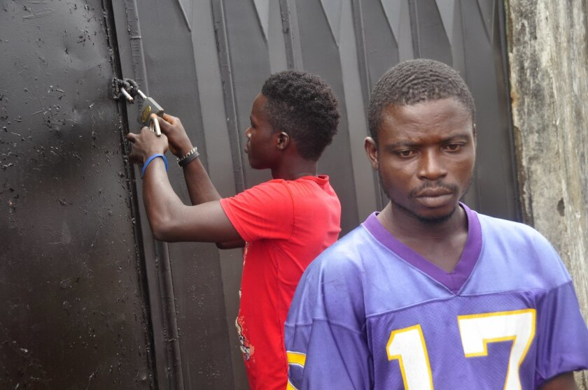 In this photo taken Saturday, March 26, 2015, community chairman Albert Reeves, foreground, at the crematorium were he used to work in Boys Town on the outskirts of Monrovia, Liberia. As Liberia marks the second anniversary Wednesday of its first confirmed Ebola cases, many neighbors say they want to see the crematorium torn down so they can try to forget that terrible time. (AP Photo/ Abbas Dulleh)