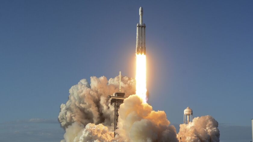 A SpaceX Falcon Heavy rocket carrying a communication satellite lifts off from pad 39A at the Kenned