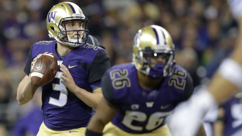 Washington quarterback Jake Browning looks to pass behind running back Salvon Ahmed during the secon