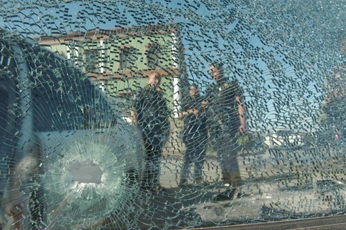 A group of experts inspect a vehicle after an armed assault in Tijuana.