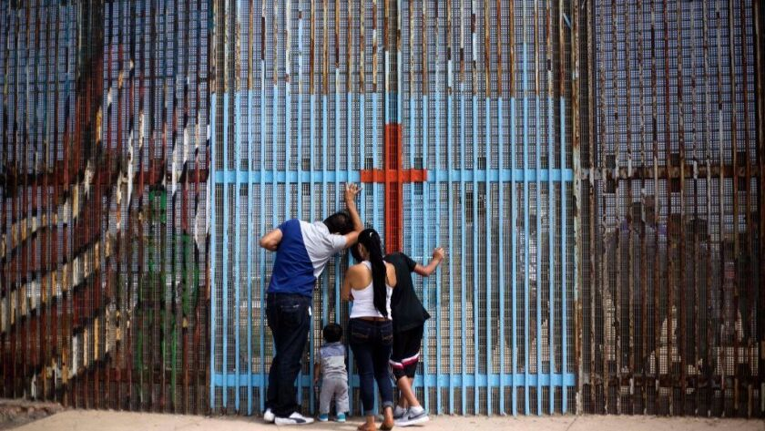 A family talks with with relatives through the US - Mexico border fence in Playas de Tijuana, in Tijuana, northwestern Mexico, on July 2, 2016.