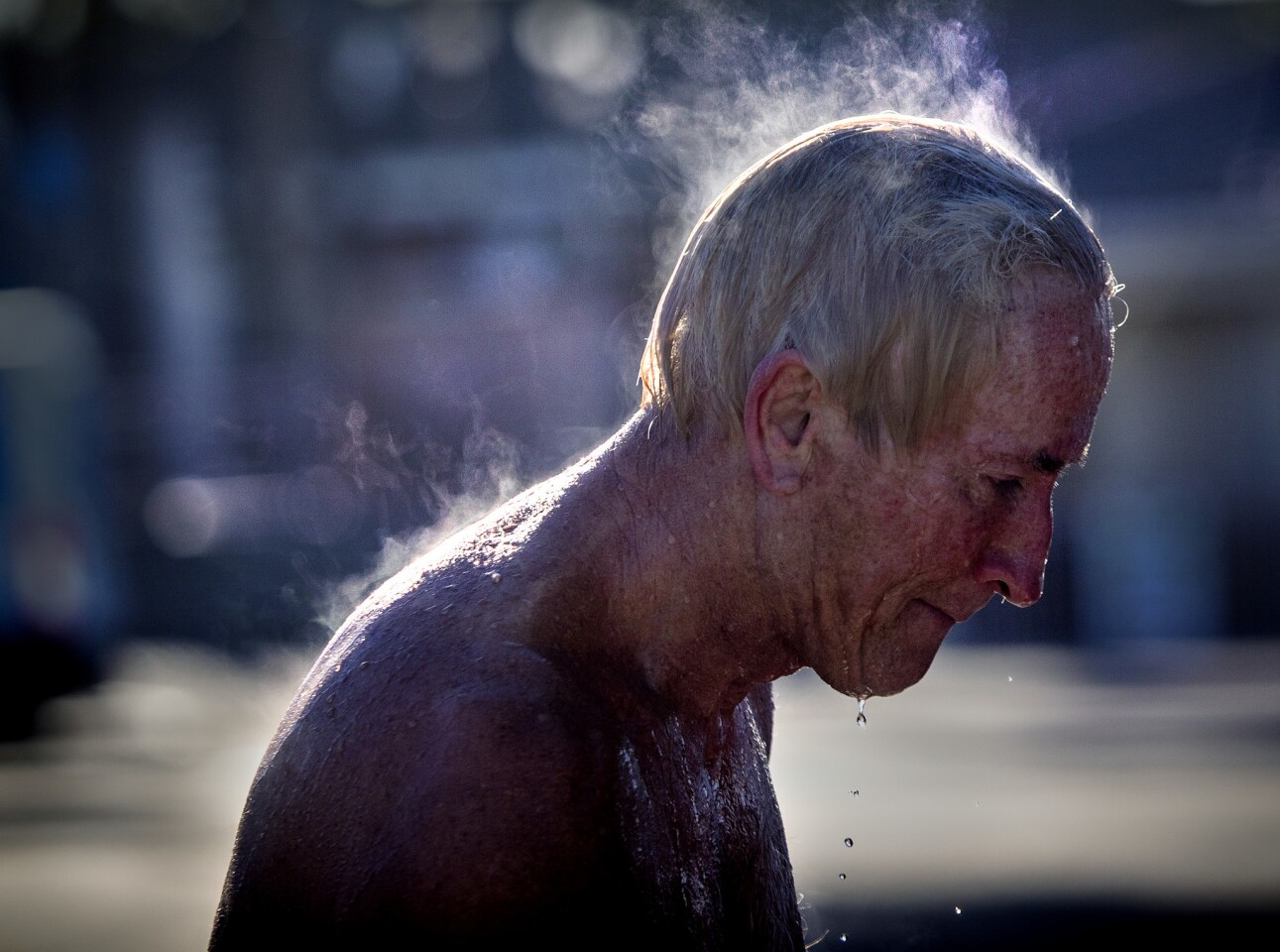 """Steam rises off Rick Rzeszewski of Tustin after he poured hot water over his head following a surf outing amid frigid air and cold water temperatures at sunrise in Huntington Beach. """"After being in that cold water, it feels wonderful,"""" said Rzeszewski, a pastor who surfs early in the morning before the crowds arrive."""