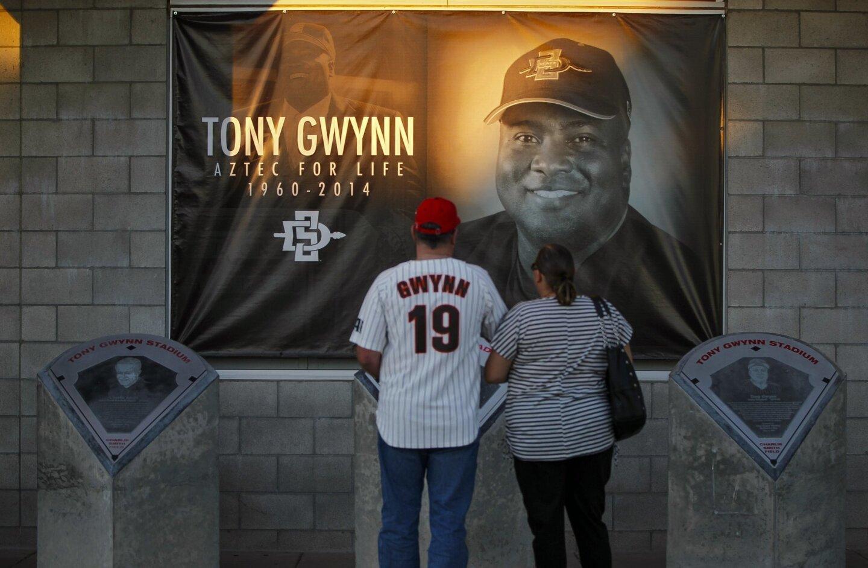 Longtime Tony Gwynn fan Mark Crews and his daughter Jennifer Crews look up a banner commemorating former Aztecs baseball coach and player Tony Gwynn.