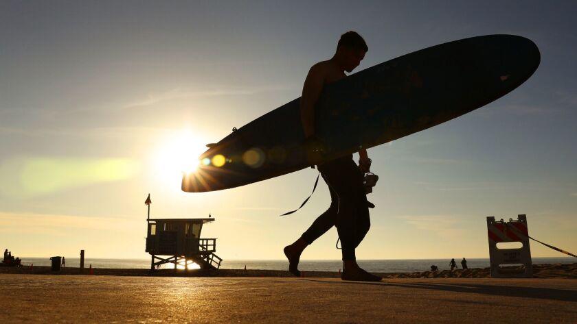 REDONDO BEACH-CA-FEBRUARY 4, 2018: A surfer in Redondo Beach walks past the setting sun on Sunday, F