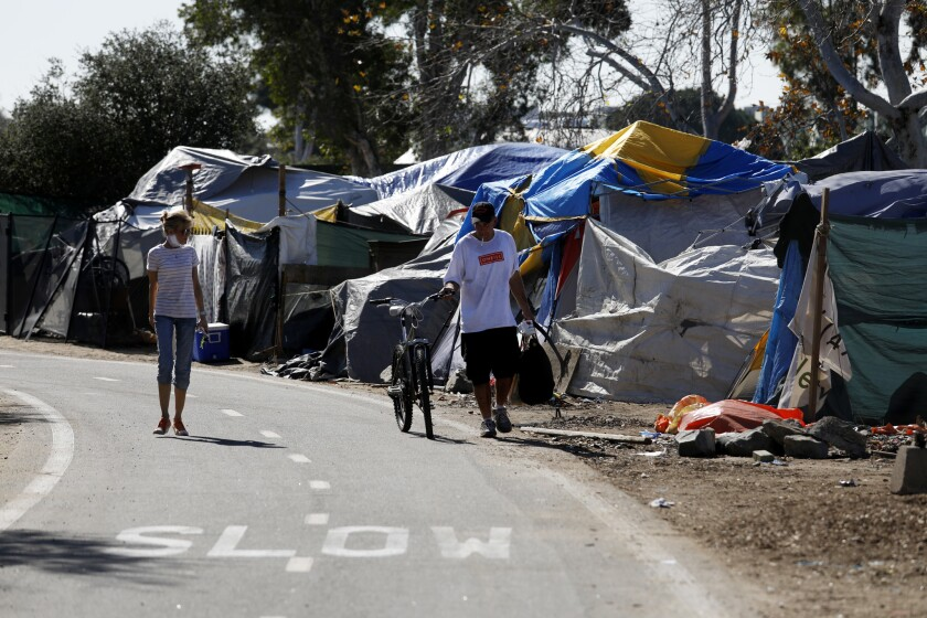 In this 2018 file photo, a homeless man and woman walk along an encampment at the Santa Ana river trail in Orange County. County officials have entered into an agreement with a hotel operator to house and treat unsheltered people amid the coronavirus.