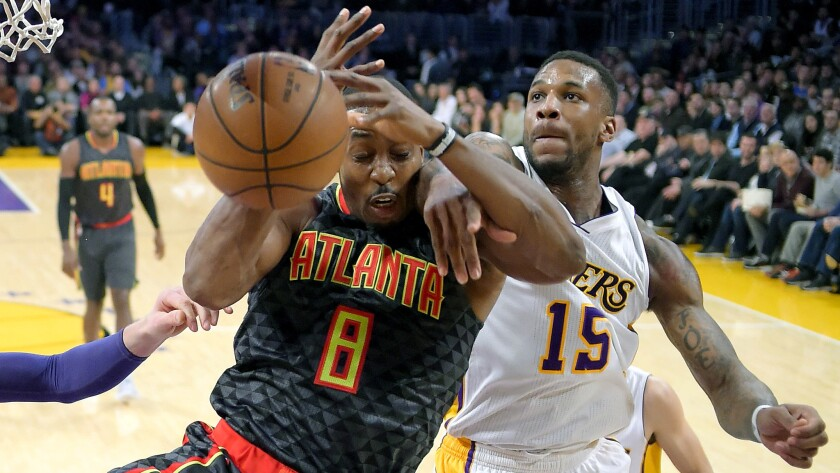 Hawks center Dwight Howard (8) and Lakers forward Thomas Robinson battle for a rebound during the first half Sunday.