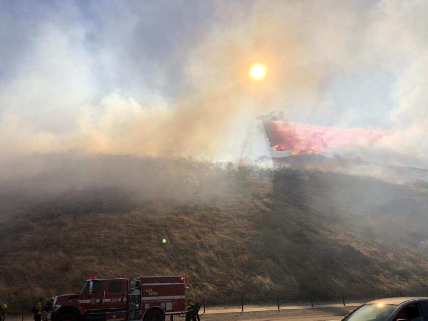 A firefighting aircraft drops retardant on a blaze Thursday afternoon just off I-15 near Gopher Canyon Road.