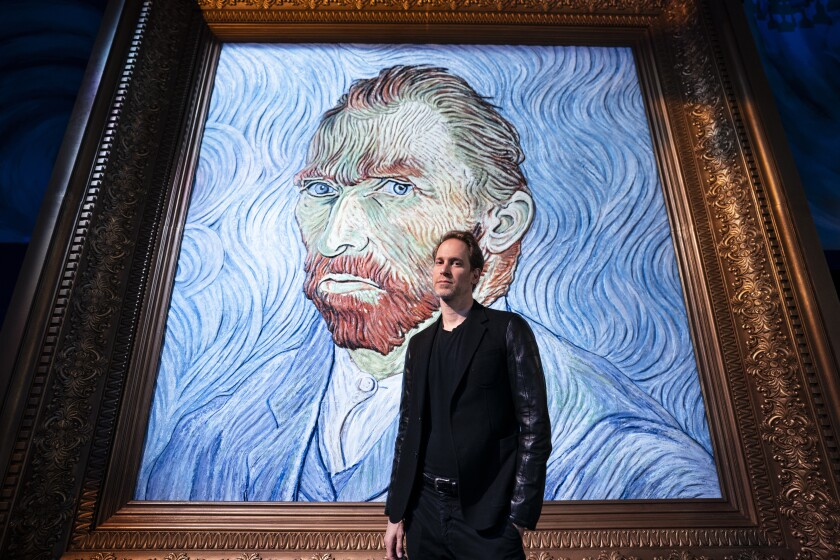 """David Korins stands beside a giant replica of celebrated painter Vincent Van Gogh's self portrait at a preview of the Immersive Van Gogh exhibit at Pier 36, Friday, June 4, 2021, in New York. Korins has added a ceiling installation that uses almost 8,000 paint brushes to thrillingly reproduce """"The Starry Night"""" and a station that uses artificial intelligence to give visitors an individualized letter from Van Gogh. (AP Photo/John Minchillo)"""