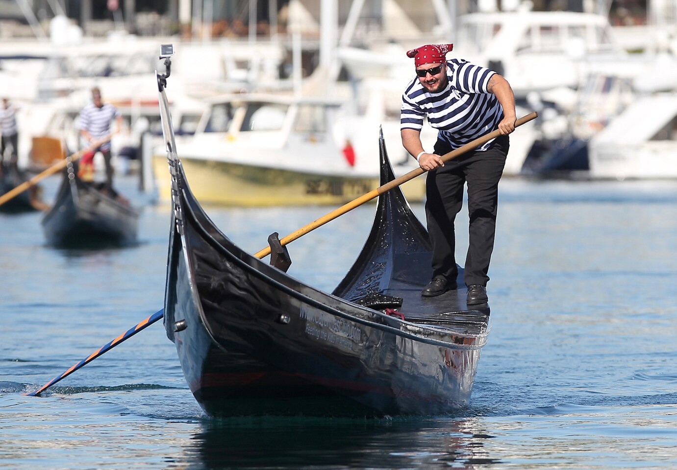 """Eric """"Enrico"""" Bender maneuvers his gondola to the finish line for first place in the first race of the day during the fourth annual U.S. Gondola Nationals held at the Bahia Corinthian Yacht Club on Saturday."""